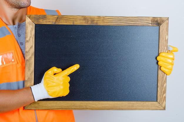 Männlicher baumeister in uniform, handschuhe, die etwas auf tafel zeigen, vorderansicht. Kostenlose Fotos