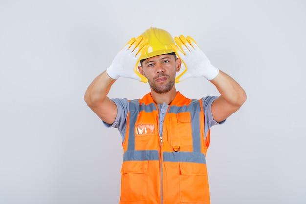 Männlicher baumeister in uniform, helm, handschuhe, die fingerrahmen gestikulieren, vorderansicht. Kostenlose Fotos