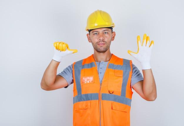 Männlicher baumeister in uniform, helm, handschuhe mit der nummer sechs mit den fingern, vorderansicht. Kostenlose Fotos