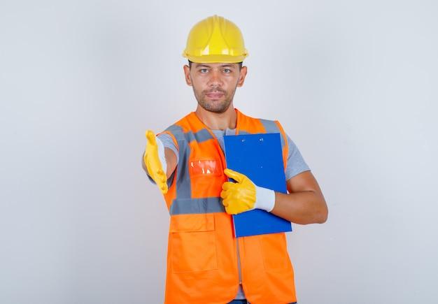 Männlicher baumeister in uniform, helm, handschuhe mit händedruck mit zwischenablage in der hand, vorderansicht. Kostenlose Fotos