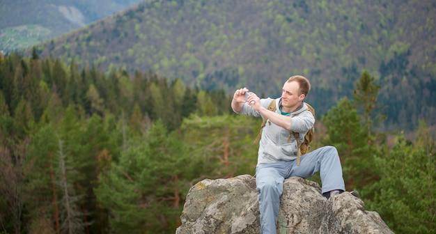 Männlicher bergsteiger mit braunem rucksack auf der spitze des felsens Premium Fotos