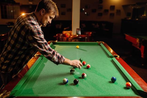 Männlicher billardspieler legt bälle auf grünen tisch, poolrauminnenraum. mann spielt amerikanisches poolspiel in der sportbar Premium Fotos