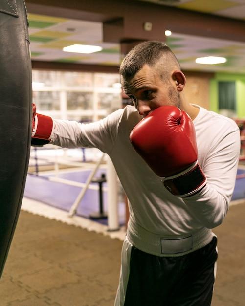 Männlicher boxer, der mit boxsack übt Kostenlose Fotos
