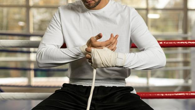Männlicher boxer, der seine hände einwickelt, bevor er im ring mit schnur trainiert Kostenlose Fotos