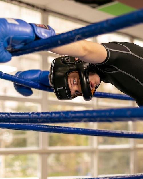 Männlicher boxer mit handschuhen und helm im ring Kostenlose Fotos