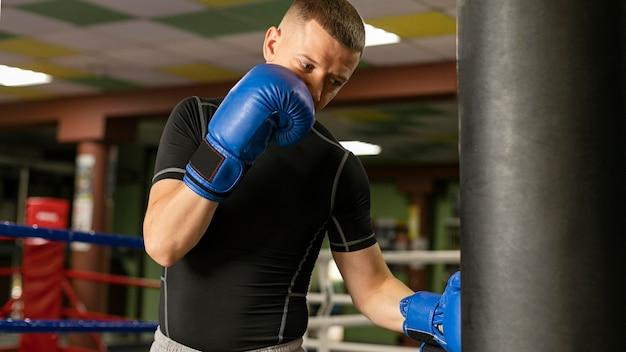 Männlicher boxer mit handschuhtraining am ring Kostenlose Fotos