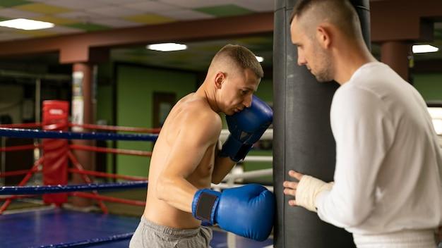 Männlicher boxer mit handschuhtraining mit mann Kostenlose Fotos