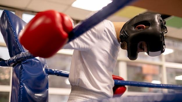 Männlicher boxer mit helm und handschuhen im ring üben Kostenlose Fotos