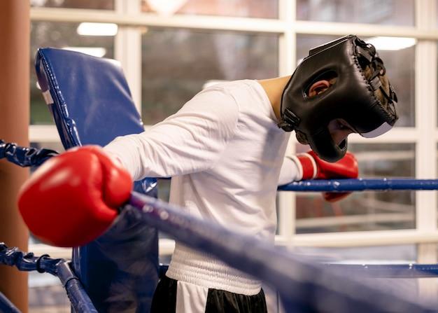 Männlicher boxer mit helm und handschuhen im ring Kostenlose Fotos