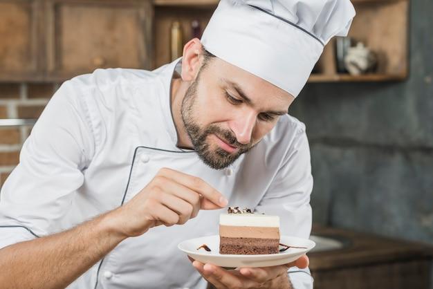 Männlicher chef, der köstlichen nachtisch auf platte verziert Kostenlose Fotos