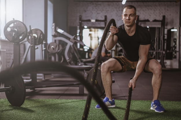 Männlicher crossfit athlet, der mit kampfseilen an der turnhalle ausarbeitet Premium Fotos