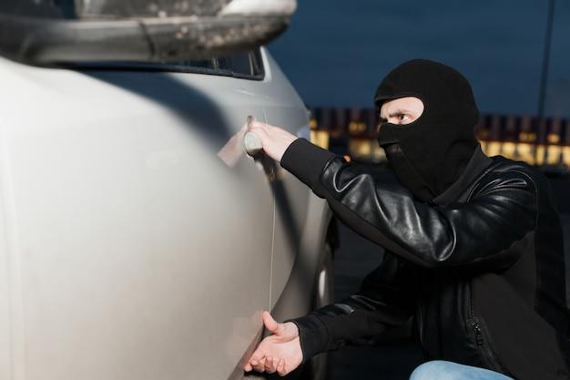 Männlicher dieb mit sturmhaube auf dem kopf, der versucht, autotür zu öffnen. carjacker fahrzeug entsperren Premium Fotos