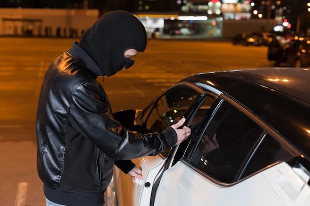 Männlicher dieb mit sturmhaube auf kopf, der autotür öffnet Premium Fotos