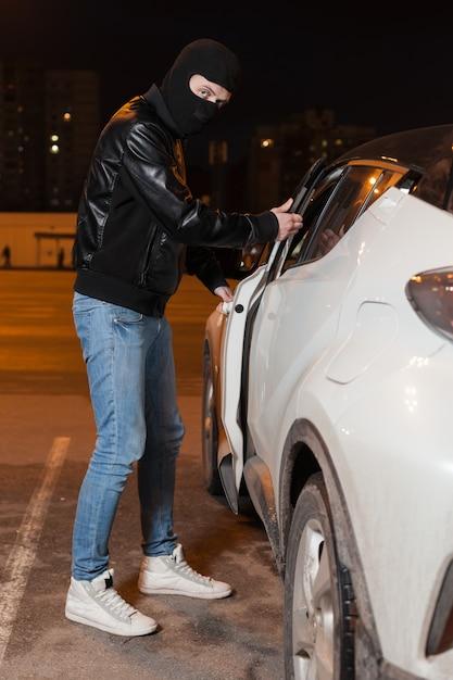 Männlicher dieb mit sturmhaube auf seinem kopf, der autotür öffnet. carjacking-gefahr, marketingkonzept für autoversicherungen. Premium Fotos