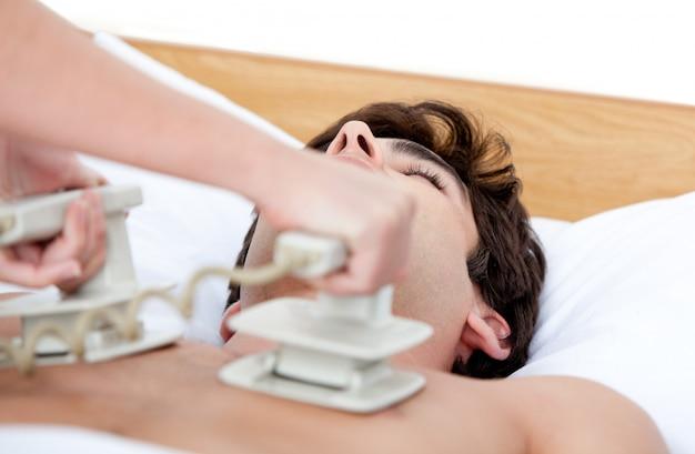 Männlicher doktor, der den defibrillator verwendet, um einen unachtsamen patienten wiederzubeleben Premium Fotos