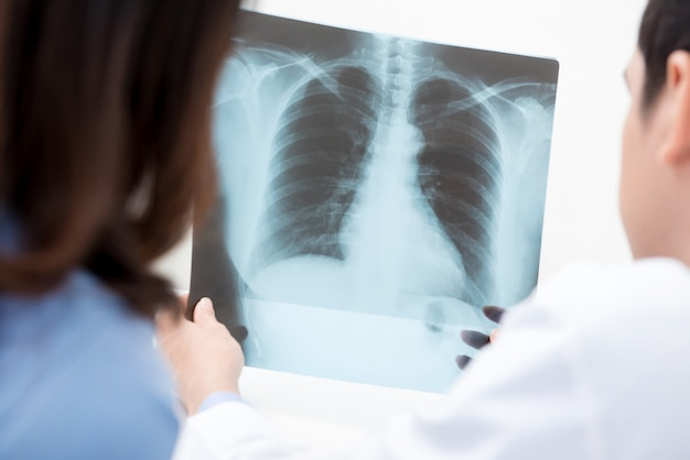 Männlicher doktor, der einem weiblichen patienten röntgenstrahl zeigt Premium Fotos