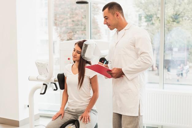 Männlicher doktor, der geduldigen zustand auf klemmbrett schreibt Kostenlose Fotos