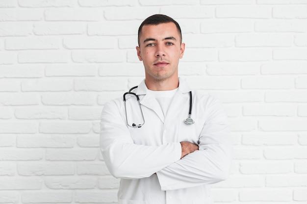 Männlicher doktor, der vor weißer backsteinmauer aufwirft Kostenlose Fotos