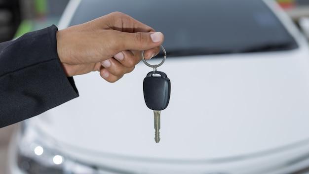 Männlicher erwachsener geschäftsmann in einer klage und halten eines autoschlüssels in seiner hand Premium Fotos
