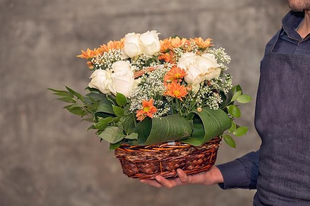 Männlicher florist, der einen blumenblumenstrauß innerhalb des korbes fördert. Kostenlose Fotos