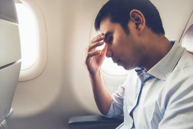 Männlicher fluggast, der im flugzeug flugkrankheit hat Premium Fotos