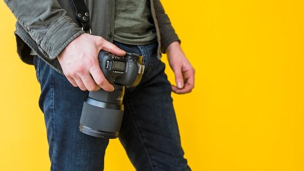 Männlicher fotograf, der mit kamera steht Kostenlose Fotos