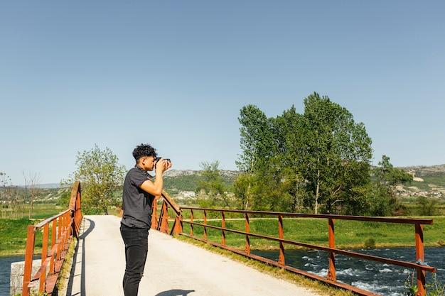 Männlicher fotografentourist mit kamera schießt schöne natur Kostenlose Fotos