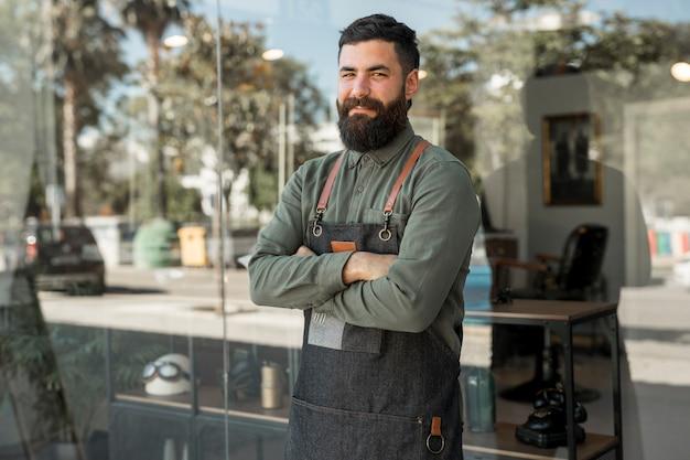 Männlicher friseur des hippies, der nahen friseursalon steht Kostenlose Fotos