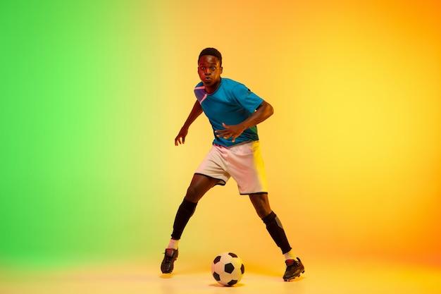 Männlicher fußball, fußballspielertraining in aktion lokalisiert auf gradientenstudio im neonlicht Kostenlose Fotos