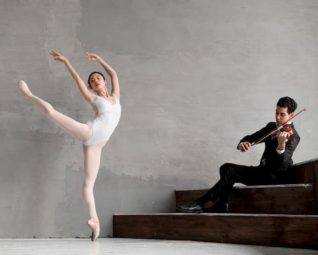 Männlicher geiger, der musik für ballerina spielt Kostenlose Fotos