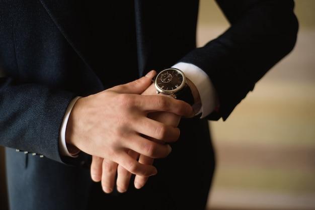 Männlicher geschäftsmann kleidet und justiert seine uhr und bereitet sich für eine sitzung vor. uhr Premium Fotos