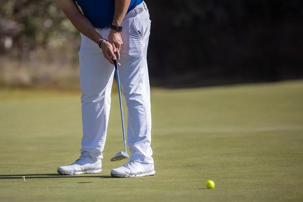 Männlicher golfspieler, der den ball mit weißen schuhen schlägt Premium Fotos