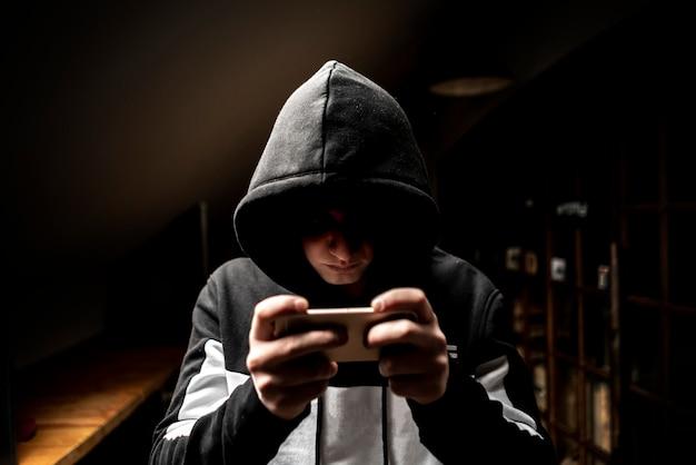 Männlicher hacker in der haube unter verwendung eines handys, ihre persönlichen daten stehlend Premium Fotos