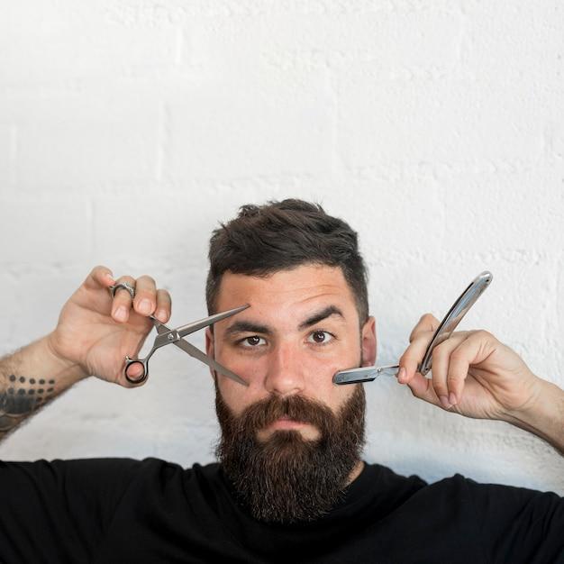Männlicher hippie, der friseurwerkzeuge zeigt Kostenlose Fotos