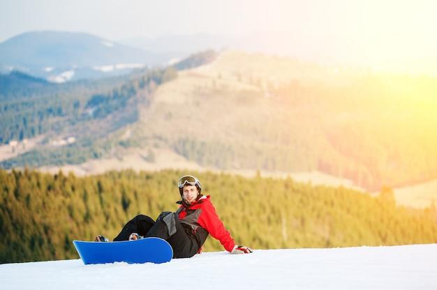Männlicher internatsschüler auf seinem snowboard am winer erholungsort Premium Fotos