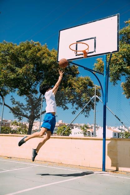 Männlicher jugendlich student, der basketballsprungsschuß macht Kostenlose Fotos