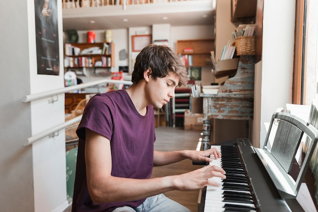 Männlicher jugendlicher, der klavier spielt Kostenlose Fotos