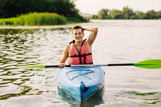 Männlicher kayaker, der auf kajak über dem idyllischen see schwimmt Kostenlose Fotos