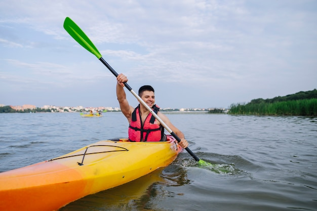 Männlicher kayaker, der kajak auf see schaufelt Kostenlose Fotos