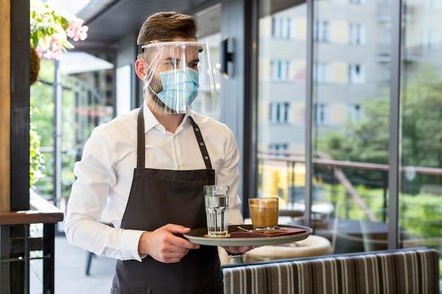 Männlicher kellner, der maske trägt Kostenlose Fotos