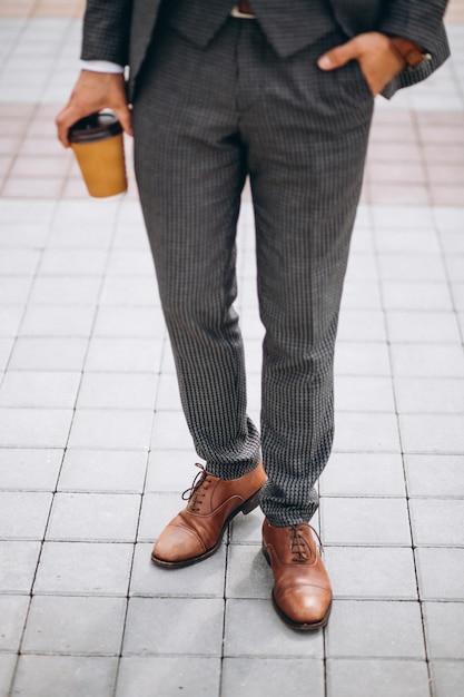 Männlicher klagenabschluß, der oben in der hand kaffee hält Kostenlose Fotos