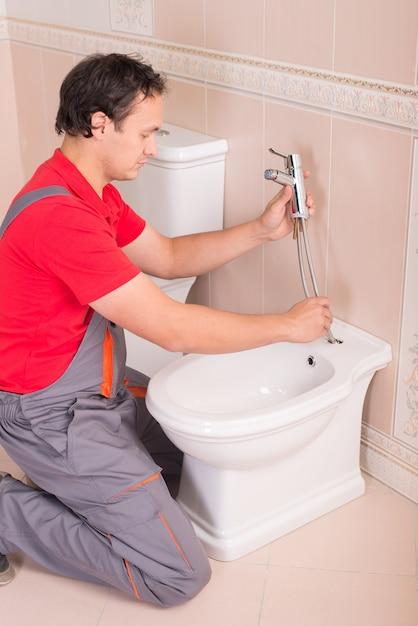 Männlicher klempner, der toilette in der wohnung repariert. Premium Fotos