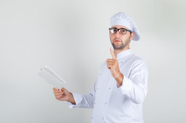 Männlicher koch in weißer uniform, brille, die buch mit wartender geste hält Kostenlose Fotos