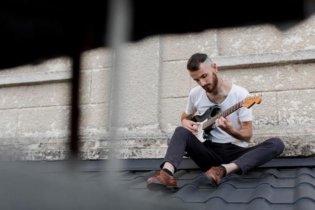 Männlicher künstler auf dach, der e-gitarre spielt Kostenlose Fotos