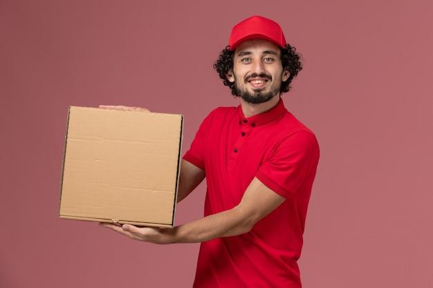 Männlicher kurier der vorderansicht im roten hemd und im umhang, die lieferung-nahrungsmittelbox auf der hellrosa wand halten Kostenlose Fotos