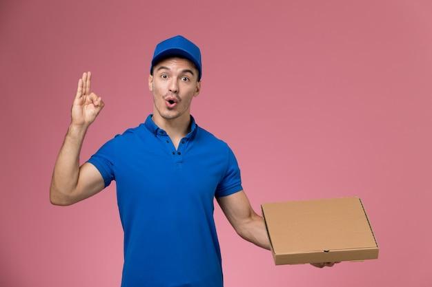Männlicher kurier der vorderansicht in der blauen uniform, die nahrungsmittelbox hält, die auf der rosa wand, dienstarbeiteruniformdienstlieferung aufwirft Kostenlose Fotos