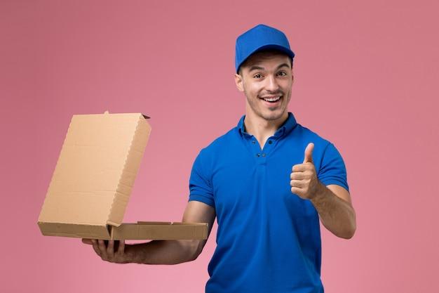 Männlicher kurier der vorderansicht in der blauen uniform, die nahrungsmittelbox lächelnd auf der rosa wand, dienstarbeiteruniformdienstlieferung hält Kostenlose Fotos