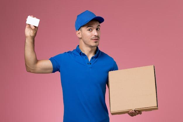 Männlicher kurier der vorderansicht in der blauen uniform, die nahrungsmittelbox mit karte auf der rosa wand hält, arbeitsuniform-dienstlieferung Kostenlose Fotos