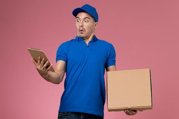 Männlicher kurier der vorderansicht in der blauen uniform, die nahrungsmittelbox mit notizblock auf der rosa wand hält, arbeitsuniform-dienstlieferung Kostenlose Fotos
