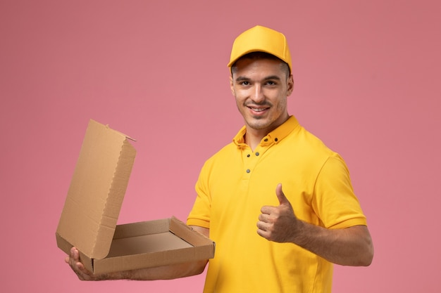 Männlicher kurier der vorderansicht in der gelben einheitlichen halte- und öffnungsnahrungsmittel-lieferbox lächelnd auf hellrosa hintergrund Kostenlose Fotos